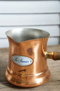 // vintage copper and wood handle sauce/milk pourer    // french enamel label on front    // good vintage condition with age blemishes that can be polished    // size: 4.5h x 9.5w    // thank you for shopping oliver and rust vintage    // PLEASE READ SHOP POLICIES PRIOR TO PURCHASE