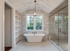 Love this master bath: tub underneath the window, large glass enclosed shower and shelving.
