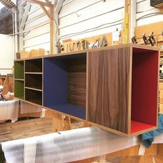 Walnut plywood wall-mounted bookcase with custom color laminate by Kerf Design kerfdesign.com