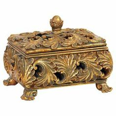 "Footed trinket box with a scrolling leaf design.    Product: Trinket box    Construction Material: Composite wood    Color: Gold     Features: Leaf design        Dimensions: 6.25"" H x 7.5"" W"