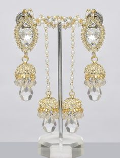 Jhumka earrings in gold finish studded with shining white color stones all over, finished with crystal drop.