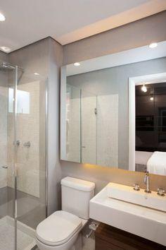O banheiro compacto tem louças brancas, espelho amplo, box de vidro e revestimentos cimentício e de pastilhas de vidro em cores neutras
