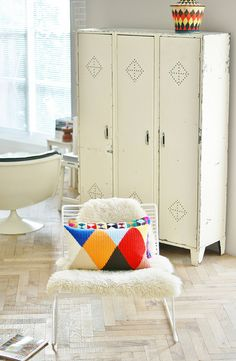 wood and wool stool diamond and triangle harlequin inspired crochet cushions and vintage white lockers