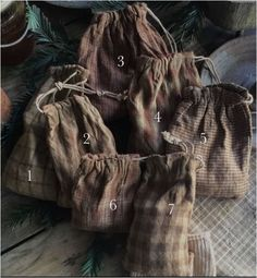 Primitive brown homespun seed bags. All great tones and fun to mix and match. One is brown ticking. Fun for your country peg rack or anywhere! #1 is 6 1/2 by 3 1/2. #2 is 5 1/4 by 3 3/8. #3 is 5 1/2 by 5 1/2. #4 is 5 1/4 by 4 1/2. #5 measures 5 1/4 by 4. #6 3 3/4 by 3. #7 5 1/4 by 3 inches. Fill em up with beans so they hang nice. Aged for a time worn look. $11 each plus first class mail.   SOLD 1,6&7 available