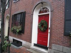 Red door on brick house with black shutters -