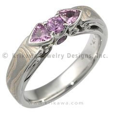 Champagne Pink Sapphire Mokume Wedding Band - This unique wedding band was handcrafted in our studio and is one-of-a-kind. It features a unique mokume gane formula. - This unusual mokume wedding band is inlaid with our Champagne formula. A heavy etch emphasizes the different layers and gives texture to the mokume gane. On top of the ring is a 2.7 mm round pink sapphire and 3 mm trilliants. Additional sapphires accent the finger hole profile; please note that one of these has a small chip…