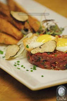 Venison Tartar with fried quail egg, shallots, shaved white truffle, and foie gras brushed french bread.  By Executive Chef Jefferey Savage, Kennebunk, Maine