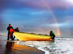 St Ayles skiff from Row Porty rowing club comes to shore after a dawn row today on Portobello beach in Edinburgh