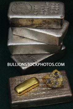 Stacked silver ingots, one troy ounce gold bar and natural gold in quartz specimen from Nevada USA.