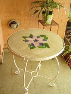 Mesa de cemento alisado blanco y aplicaciones de vidrio de vitral formando una flor y patas de hierro forjado.