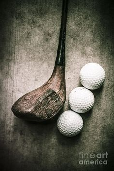 Traditional wooden golf club with balls on grunge cement surface. Art of golfing by Ryan Jorgensen