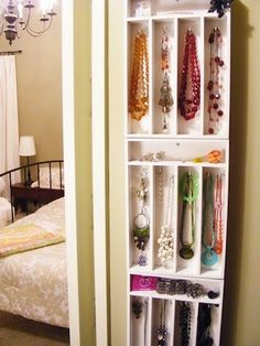 Cutlery trays painted white, hooks added for hanging necklaces, attached to the wall to create a tall shelf look.