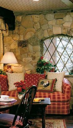 How cozy and friendly is this living space! Love the window and the stone walls.