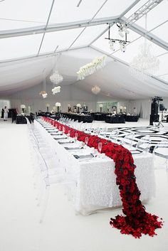 Modern and amazing! Long head table with a deep red floral runner on a tablecloth made of thousands of square white sequins. ~ https://www.insideweddings.com/weddings/black-and-white-modern-wedding-with-unique-details-in-cincinnati/698/