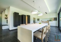 Keuken ontwerp door interieurarchitect Ken Creemers (www.cr33mers.be). Gebruikte materialen: Corian tafel, Stoelen in Eik (Younic), MDF gelakte kasten, Wever&Ducré. Modern wit met accenten van zwart en hout.   Kitchen design by interior architect Ken Creemers (www.cr33mers.be).Used materials: Corain table, oak chairs (Younic). White interior with accents in black and oak.