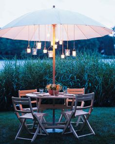 As the long summer days melt into balmy nights, ease the transition -- and extend the pleasure -- by dining outdoors under a private starry dome of twinkling candles. Hanging a set of miniature glass lanterns from your patio umbrella not only creates the effect of a magical chandelier, it also makes more table space for an inventively placed centerpiece.More Outdoor Lighting Ideas