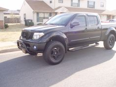 black Nissan Frontier lifted with bull bar