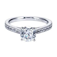 14K white gold engraved solitaire engagement ring. The round diamond engagement ring has an engraved shank with side detail. Can be customized to fit any size o