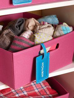 Etiquetas de equipaje de cuero, adornado con letras adhesivas, identificar qué es lo que en los contenedores de lona. Los contenedores de color rosa brillante y etiquetas azules audaces añaden un toque de color contra el blanco nítido armario organizador.