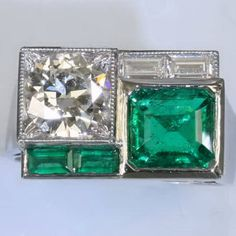 Art Deco ring featuring a rare and exceptionally fine, vivid green Colombian emerald and a large (1.28 carat) brilliant cut diamond as well as diamond and emerald baguettes. The ring itself is made in platinum