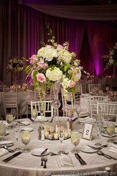 #Tall #centerpiece of #white hydrangea, peonies, #blush garden roses, and orchids accented with hanging amaranthus.