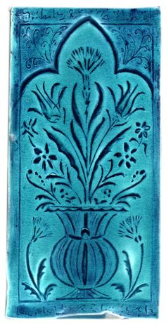 handmade tile in turquoise and cobalt blue with Turkish or Moorish flower and urn motif, hand carved