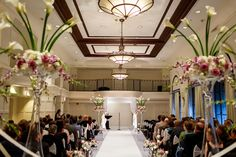 Dramatic tall arrangements of white and lavender roses with calla lilies on mirrored cubes line the ceremony. Note the smaller arrangements at the end of each row.    Warwick Allerton Hotel Chicago | Nicole Defilippis Photography