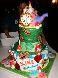 """Alice in Wonderland Cake - This cake was created for an """"Alice in Wonderland"""" themed sweet sixteen. The birthday girl's name is Aline - so the event became """"""""Aline in Wonderland"""". The teapot was created with cereal treats covered in fondant. The bottom tier cake was chocolate filled with fresh fruit and whipped cream. The middle (hat) layer was sponge cake with chocolate ganache. The cake was covered in fondant. The clock, bunny ears, playing card references, signs, tea cup, drink me bottle…"""