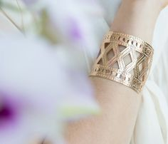 An intricately detailed rose gold cuff pairs perfectly with a t-shirt and jeans.