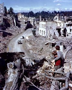 St. Lo, France — U.S. military vehicles move through the heavily damaged town of St. Lo in Normandy during the summer of 1944.