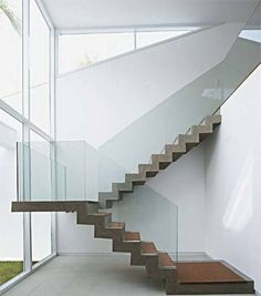 Nesta casa de praia, o efeito escultural da escada salta aos olhos. Sua estrutura é de concreto aparente, com pisada de cumaru e guarda-corpo de vidro, quase imperceptível. Projeto de Mônica Drucker.