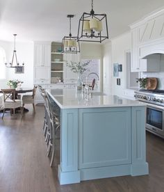 Look at this bright and cheery kitchen! French country style inspired kitchen with beautiful blue island and breakfast bar. The metal accents add a contemporary feel.