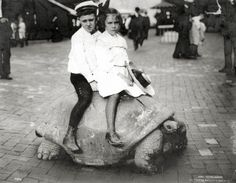 Two children riding the Giant Tortoise on the Pike at the 1904 World's Fair.