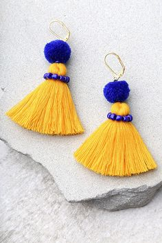 """Add a pop of fun with the Shashi Emily Blue and Yellow Tassel Earrings! Bright yellow threaded tassels dangle beneath royal blue pompoms with matching beads. Earrings measure 3"""". #Yellow"""