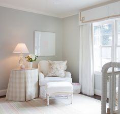 Chic girl's nursery design with soft gray walls and Greek key valance paired with white textured drapes.
