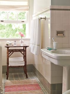 """Including a small piece of wood furniture in your bathroom is an easy way to soften and add interest to a room that is generally dominated by ceramic tile, stone and metal finishes. We like to find charming occasional tables at flea markets and stack them with crisp white towels."" —Suzanne and Lauren McGrath, authors of Good Bones, Great Pieces"