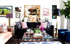 Glamorous living room with a black couch, artwork, and mix-and-matched decor pillows.