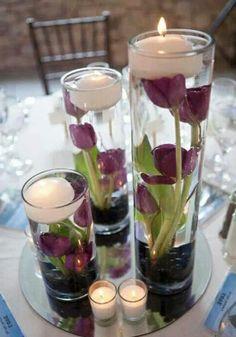 Des tulipes en violet dans l'eau et des bougies flottantes