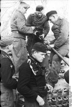 German Panzersoldaten. Northern France 1943. Crew is preparing the cleaning rod and brush for the tank's main gun.