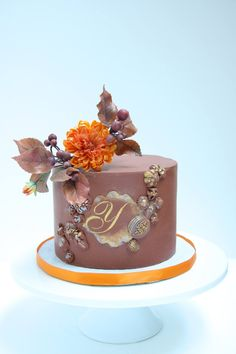 A rich colored birthday cake with vibrant orange Dallia
