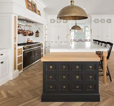 Black island, herringbone floors, brass dome pendant in white kitchen. Fox Group Construction