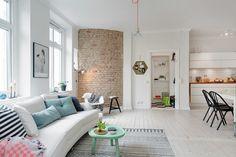 mieszkanie w otwartej zabudowie ze ścianą z czerwonej cegły w salonie,białą…