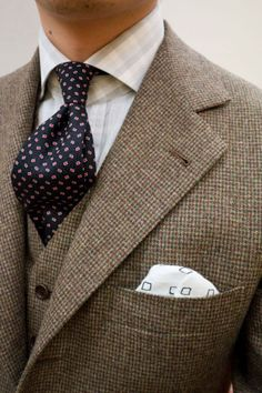 beige, green and brown houndstooth patterned three piece suit, dark blue tie with red squares, white-light grey checked shirt