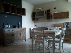Cucina in legno vecchio, stile industrial.Tavolo e sedie bianco spazzolato.