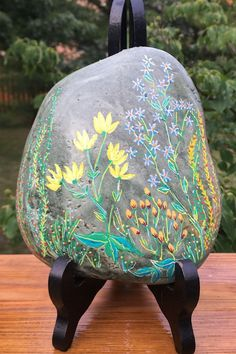 A garden of fantasy flowers covers the front of this hand painted rock. I left the background in it's natural state to accentuate it's jade-like appearance. Painted Rocks For Sale, Hand Painted Rocks, Rock Hand, Unique Housewarming Gifts, Unique Gardens, Paper Weights, Free Gifts, House Warming, Flowers