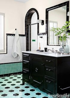 A black vanity topped with honed Calacatta Luna marble anchors the boy's bathroom. Glass pulls and knobs by House of Antique Hardware. Porcher's Mesa sink and THG faucets.  Trevor Tondro  - HouseBeautiful.com