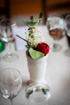 The reception table was lined with various milk-glass vases filled with different flowers, including red peonies and astilbes.
