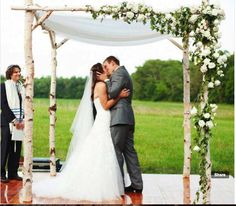 It would be a little less floral than this to keep cost down....Altar option #1: A birch chuppah will be draped with sheer ivory fabric and will feature an asymmetrical design of silver dollar eucalyptus with pops of white hydrangea and white spray roses.