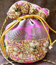 This gorgeous brocade drawstring potli bag/batwa has a floral pattern of beadwork with colored and golden beads. It has an inner lining of satin, and a thin shoulder strap as well