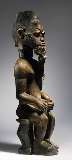 Africa | Seated male figure from the Baule people of the Ivory Coast | Wood and fiber | ca. late 19th to early 20th century